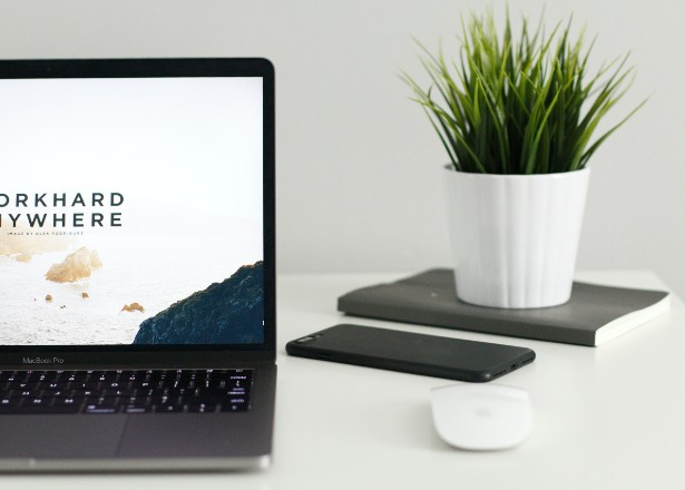 a white desk with a laptop, cellphone, notebook and small potted plant
