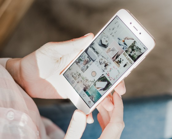 a girl holding a phone, looking at a curated feed